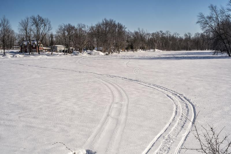 雪上电车踪影在河的 库存图片