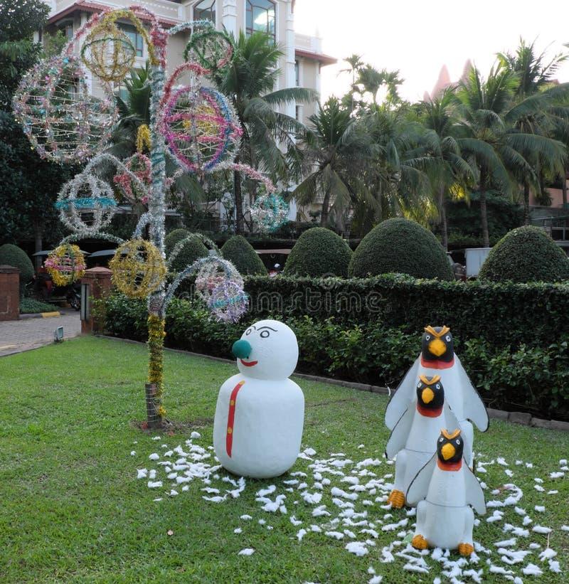 雪人和三只企鹅在一棵绿色草坪、庭院雕塑、棕榈树和装饰树 免版税库存照片