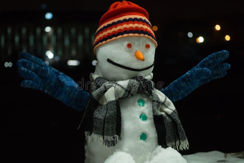 雪人 在黑暗的夜背景的滑稽的雪人,与大胆的光在背景中 新年2019年 库存照片