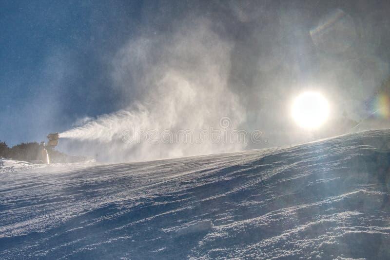雪制造商机器运转雪枪或在滑雪倾斜的雪大炮依靠-做的雪标准设备设备创造 免版税图库摄影