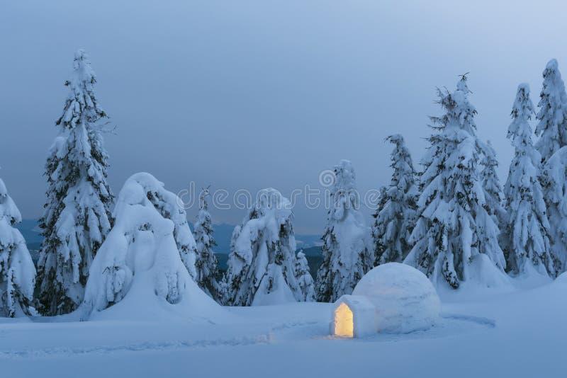 雪园屋顶的小屋光亮从里面 库存图片