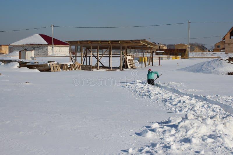雪在农厂妇女的冬天滑动了围场清除段落到雪的房子 免版税库存照片
