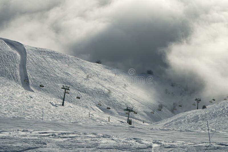 滑雪在南部的倾斜Aibga西高加索里奇的云彩倾斜在罗莎Khutor高山手段 库存照片
