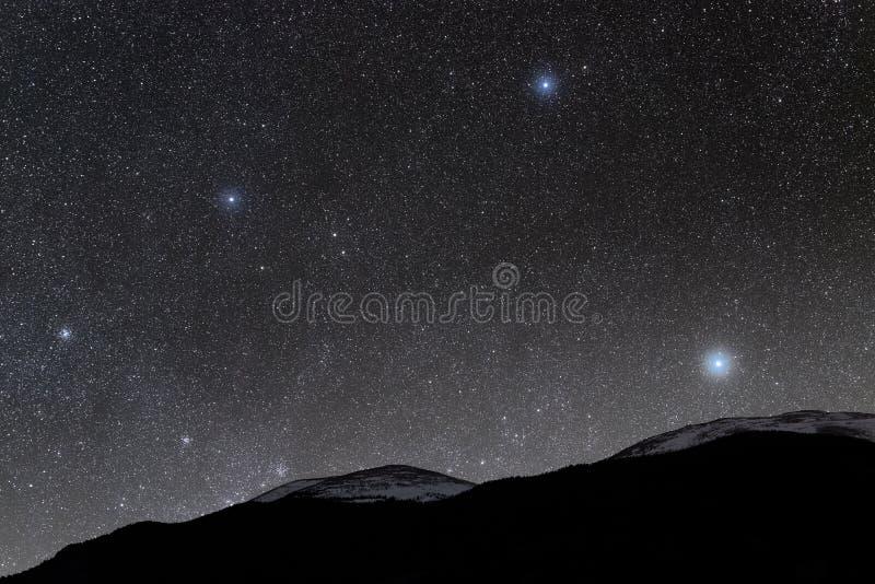 雪在星光的加盖的山 免版税库存照片