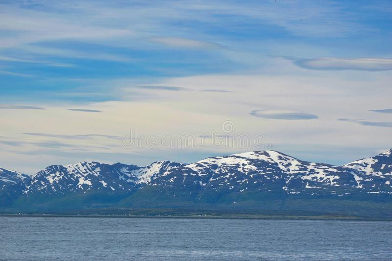 雪在特罗姆瑟附近的加盖的山 免版税图库摄影