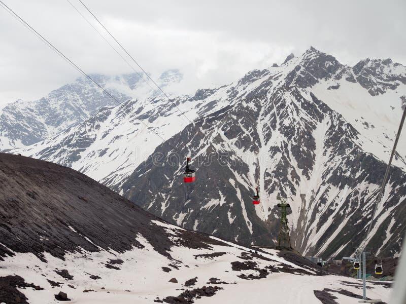雪山背景中的红色缆车 航拍 库存照片
