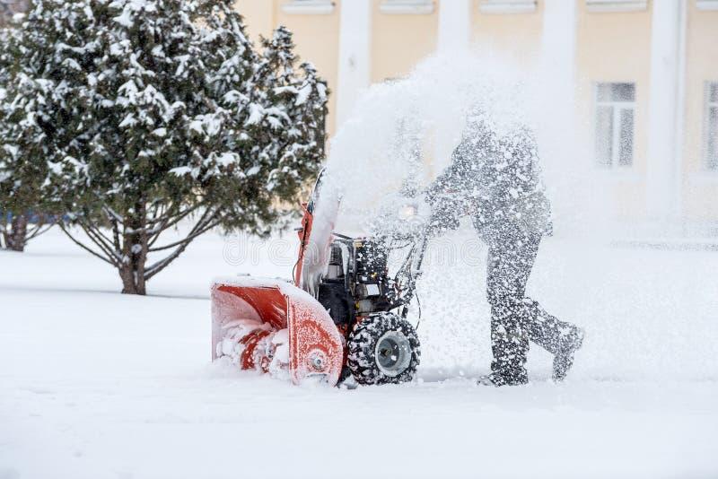 雪撤除与吹雪机一起使用 取消雪的人 重的降雨雪和雪堆 免版税库存照片