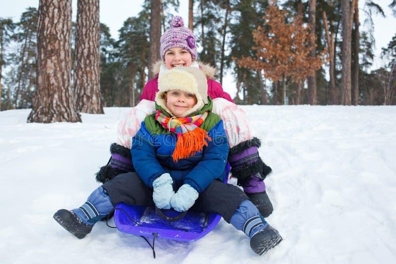 雪撬的孩子在雪 免版税库存照片
