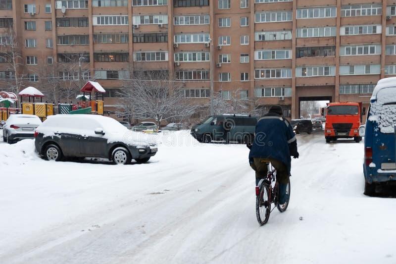 雪擦净剂骑在降雪的一辆自行车 反对背景是雪犁 积雪的清除的问题 库存照片