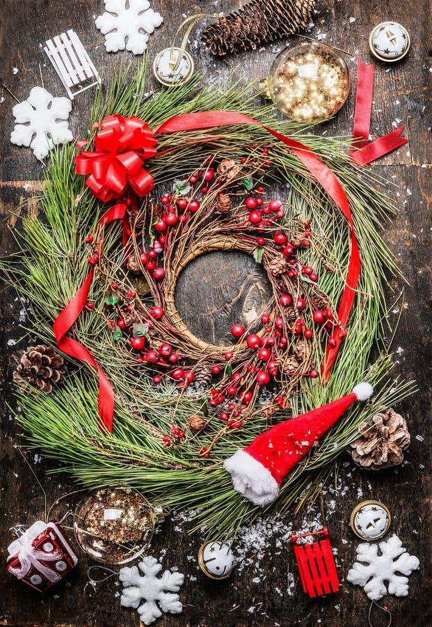 雪松圣诞节花圈用冬天莓果、丝带和假日装饰在土气木背景 免版税库存图片