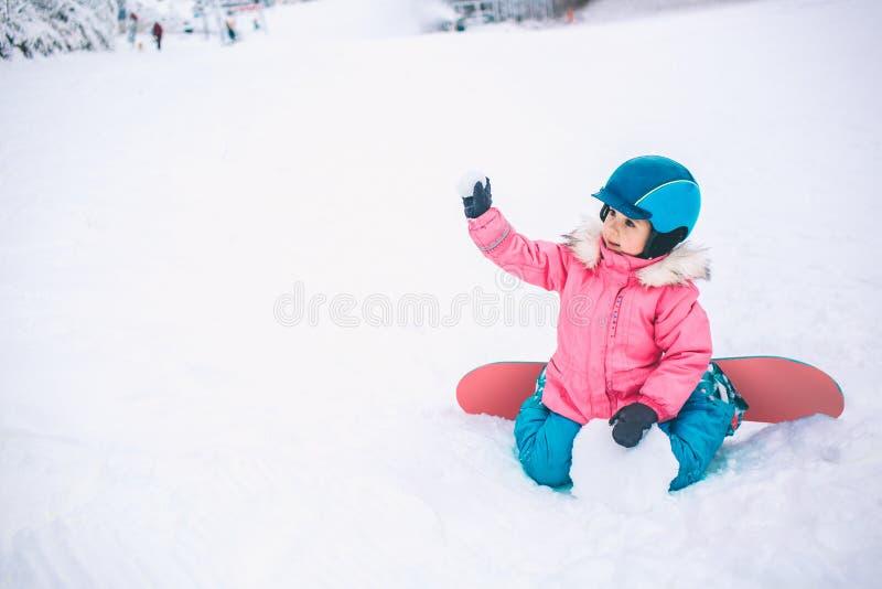 雪板冬季体育 使用与雪的小孩女孩佩带温暖的冬天穿衣 背景蓝色雪花白色冬天 免版税库存图片