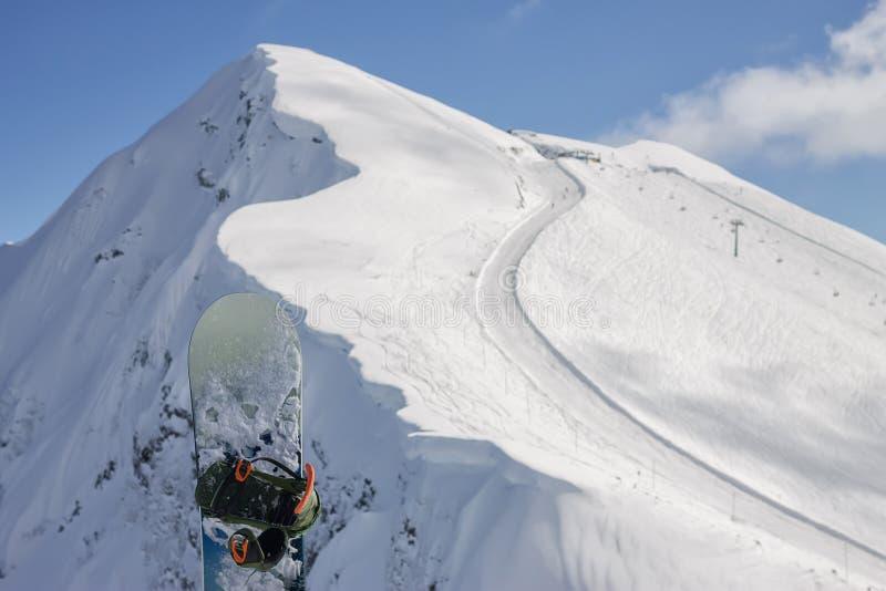 雪板在多雪的山高加索,滑雪场罗莎Khutor的背景站立 免版税库存照片