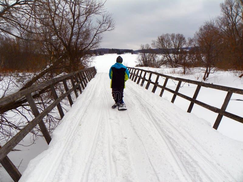 雪板横穿冬天雪上电车桥梁的孩子 库存照片