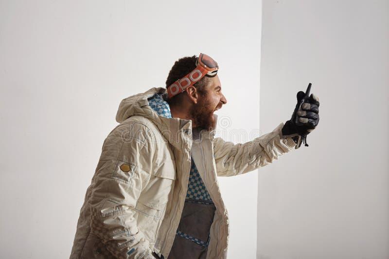 雪板齿轮的人尖叫入携带无线电话 免版税图库摄影