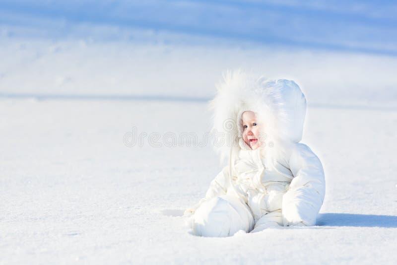 雪的愉快的笑的婴孩在晴朗的冬日 免版税库存图片