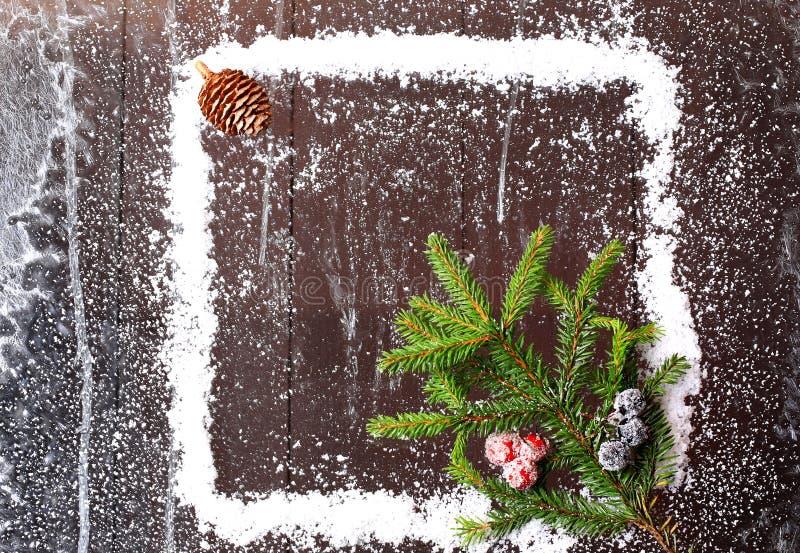 雪的框架与圣诞树的和在一个黑暗的木背景多雪的冬天小册子的爆沸 库存照片