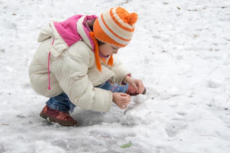雪的逗人喜爱的小女孩 免版税库存图片