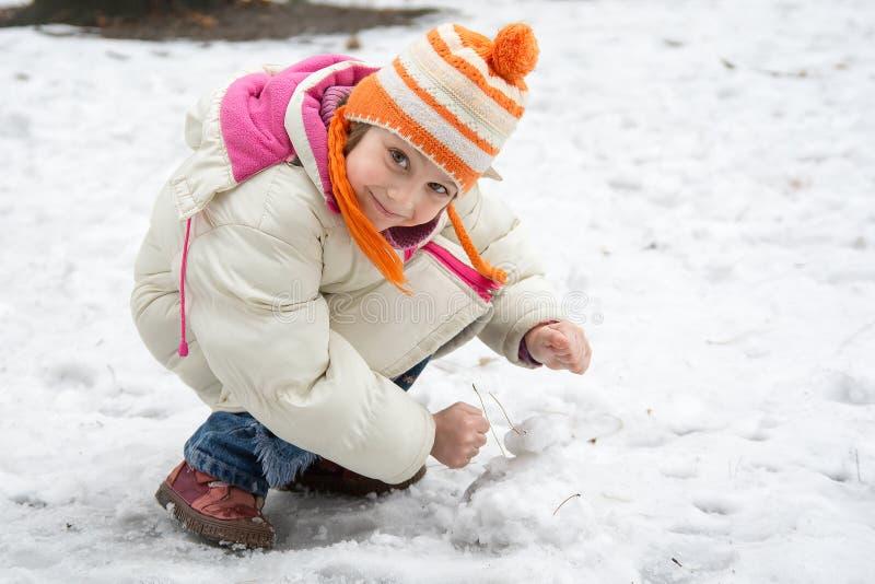 雪的逗人喜爱的小女孩 免版税库存照片