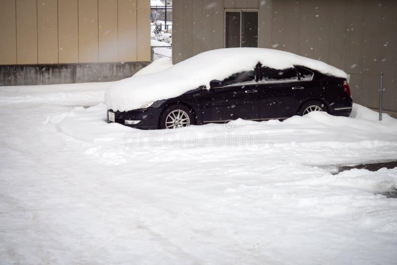 雪盖汽车屋顶在停车场 时数横向季节冬天 免版税库存照片