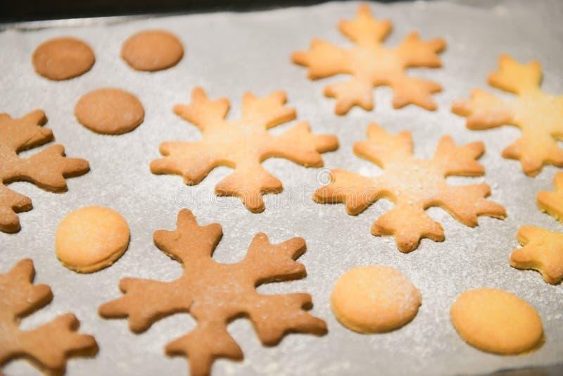 雪花曲奇饼 雪花塑造了姜饼曲奇饼堆积和栓与金弓 免版税库存照片