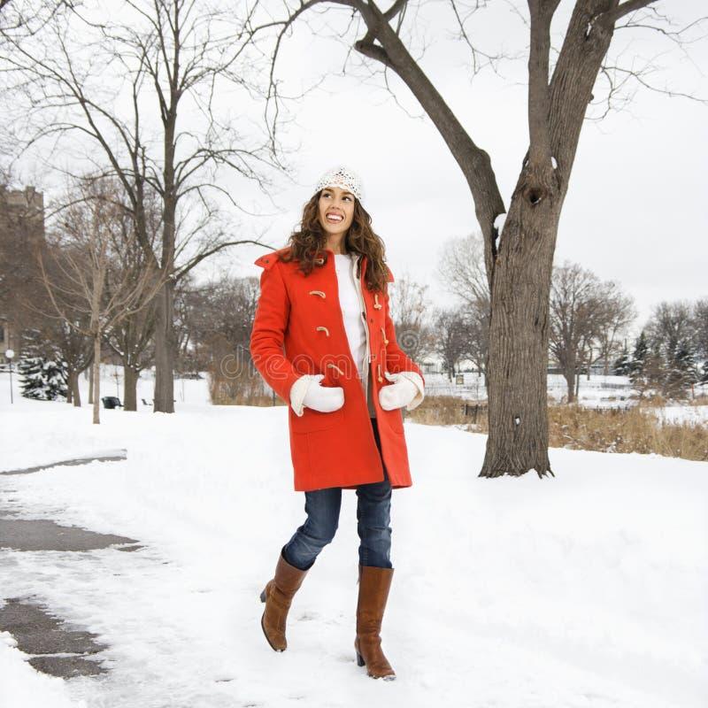 雪走的妇女 免版税库存图片