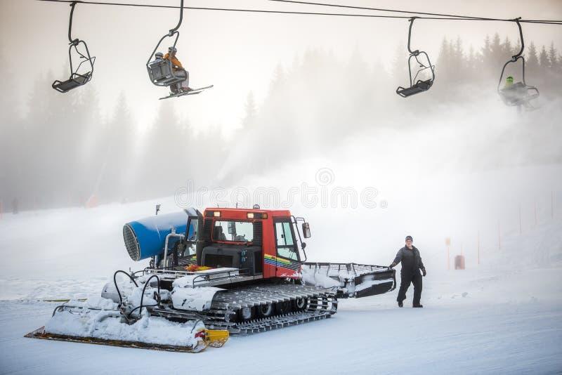 雪运转在滑雪倾斜的清洁机器在缆绳椅子下 免版税库存照片