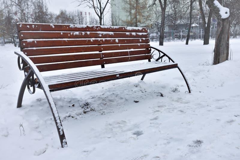 雪长凳在冬天公园,休息在公园 库存图片