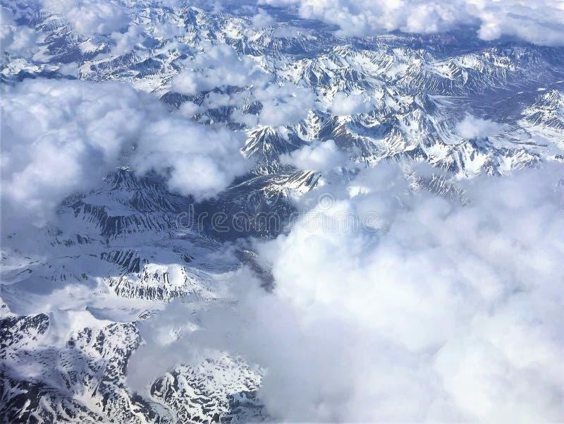 雪鸟瞰图加盖了山和云彩在阿拉斯加 免版税库存照片