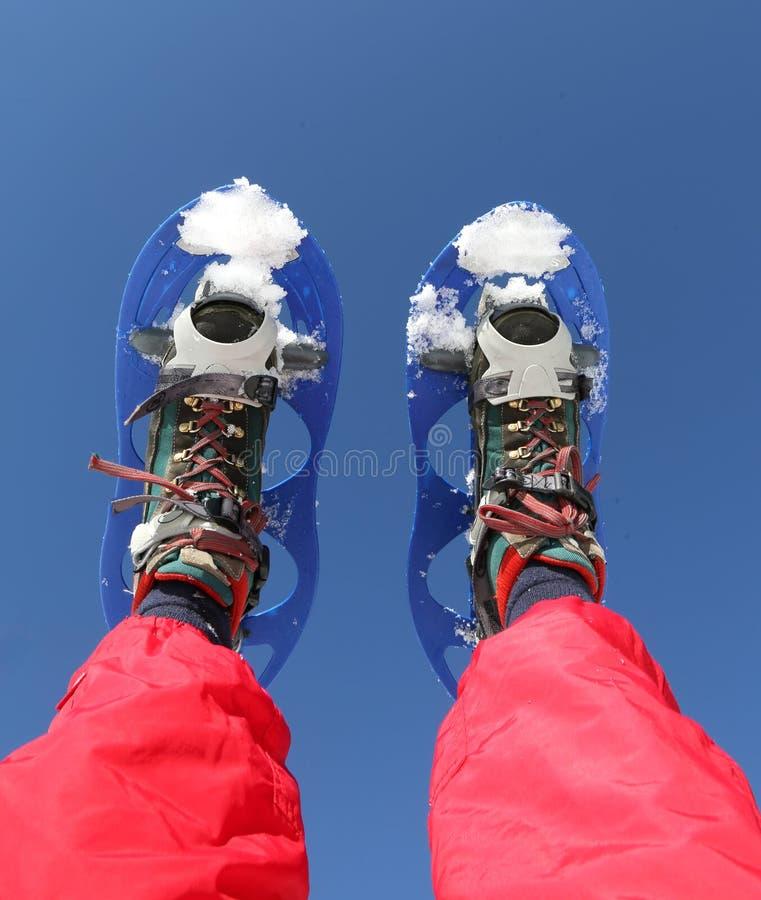 雪靴和红色滑雪服在山 免版税库存图片