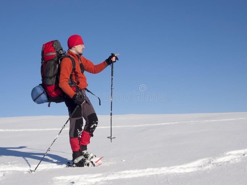 雪靴的人在山表明方向 免版税库存图片