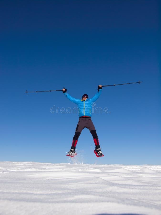 雪靴的人在山跳 免版税图库摄影