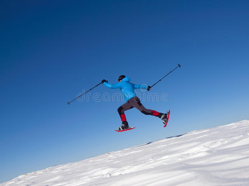 雪靴的人在山跳 免版税库存图片