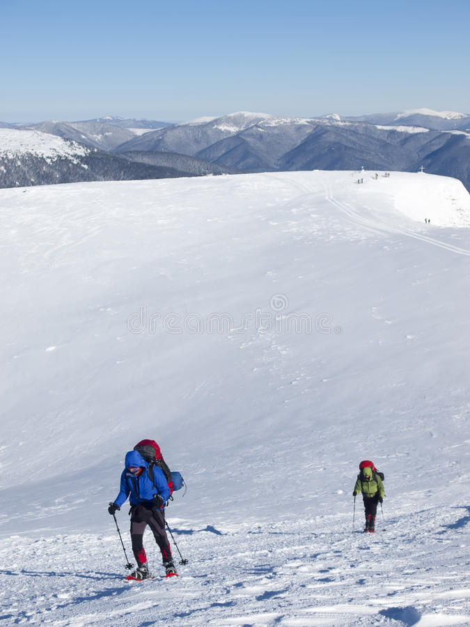 雪靴的人在山进来 免版税库存照片
