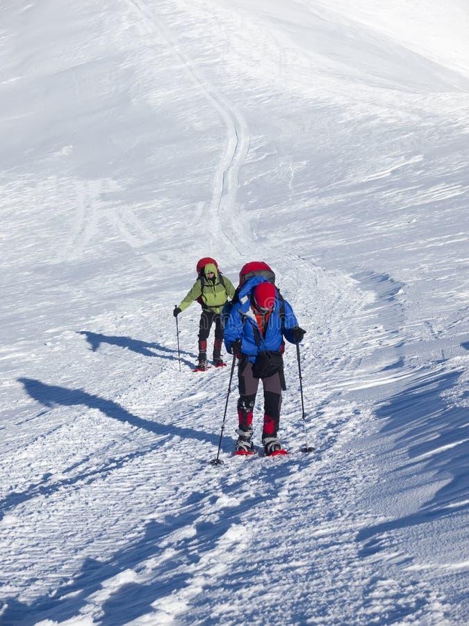 雪靴的人在山进来 免版税库存图片