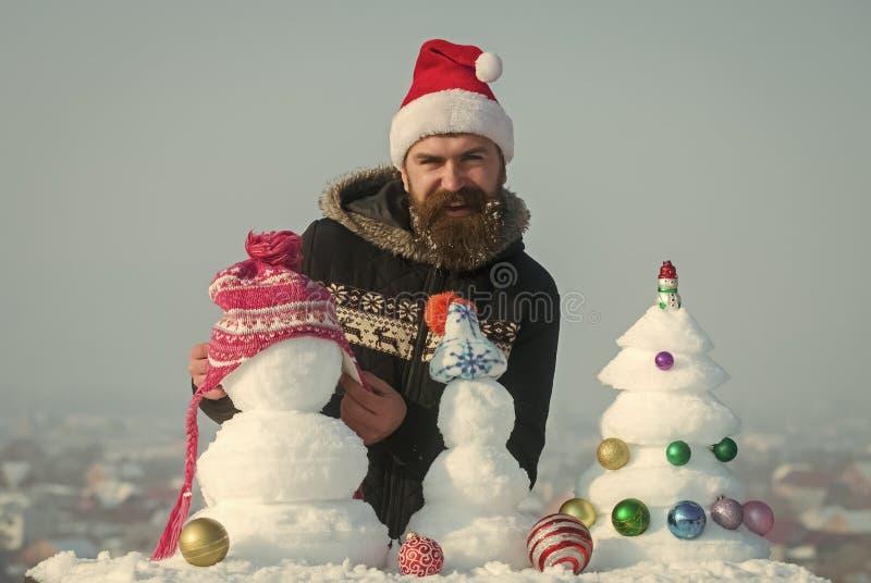 雪xmas树和雕塑在蓝天 库存照片