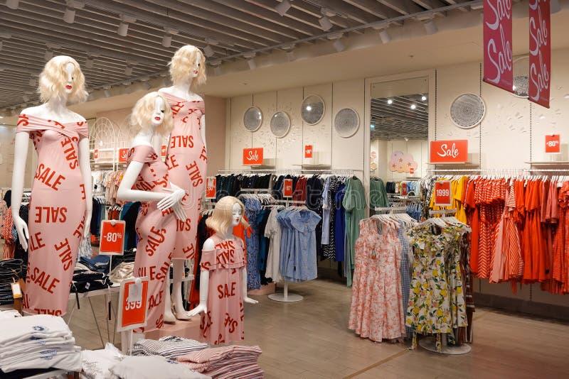 零售妇女的服装店与四个时装模特的销售显示在前景 免版税库存图片