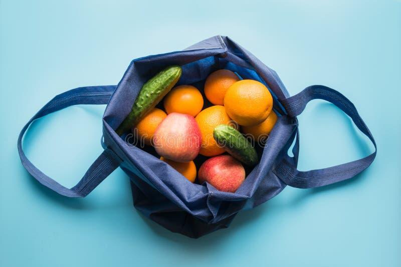零的废概念 蓝色购物的纺织品袋子用新鲜的桔子和菜 文本的空间 免版税库存照片