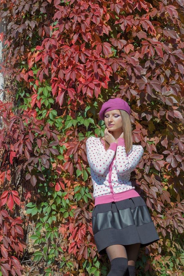 贝雷帽和裙子的美丽的甜女孩在叶子中的明亮的红颜色走在秋天公园明亮的晴天 免版税库存图片