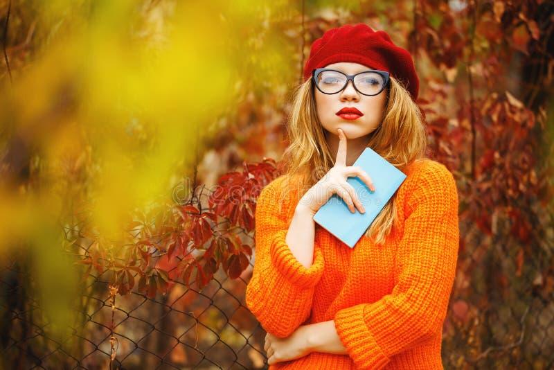 贝雷帽的可爱的女孩和毛线衣在秋天停放,拿着笔记本 图库摄影