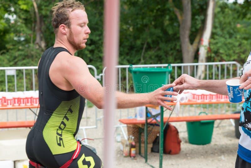 雷根斯堡,巴伐利亚,德国, 2017年8月06日,第28雷根斯堡三项全能2017年,赛跑者采取塑料杯子用水 库存照片