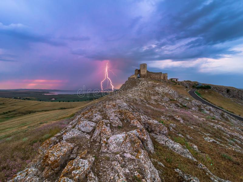 雷电,在多云晚上蓝天的闪电在老Enisala堡垒,城堡 免版税库存照片