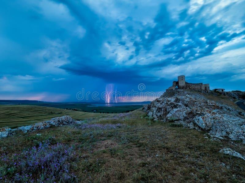 雷电,在多云晚上蓝天的闪电在老Enisala堡垒,城堡 库存图片