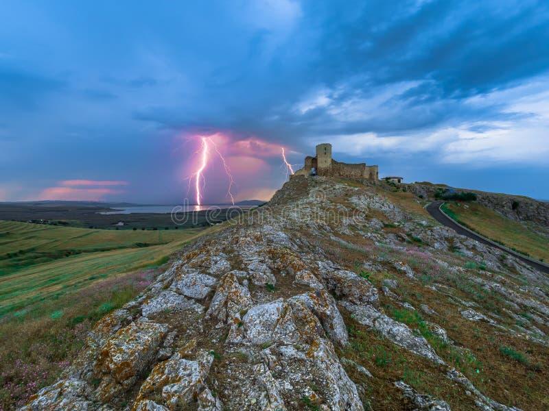雷电,在多云晚上蓝天的闪电在老Enisala堡垒,城堡 库存照片