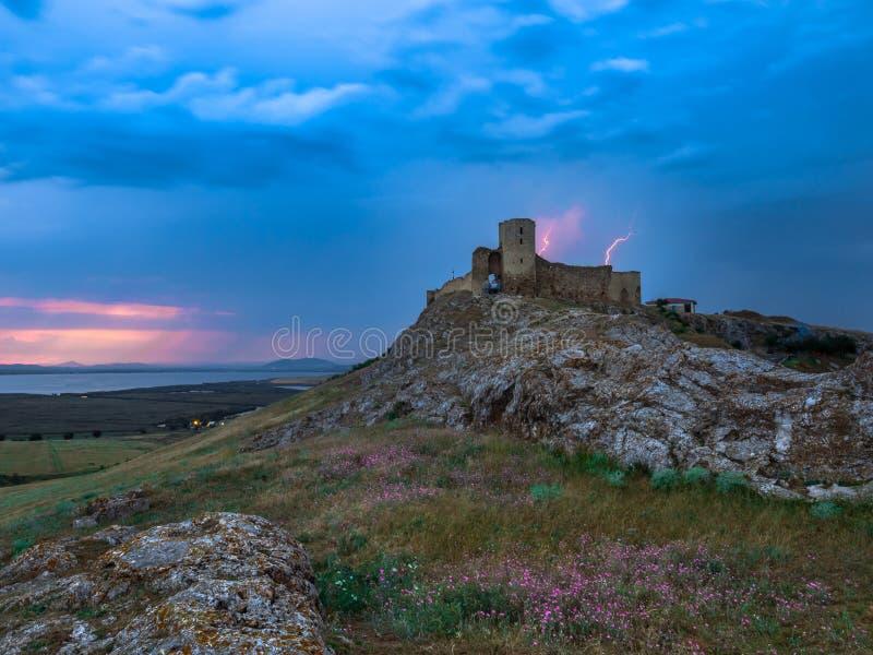 雷电,在多云晚上蓝天的闪电在老Enisala堡垒,城堡 图库摄影