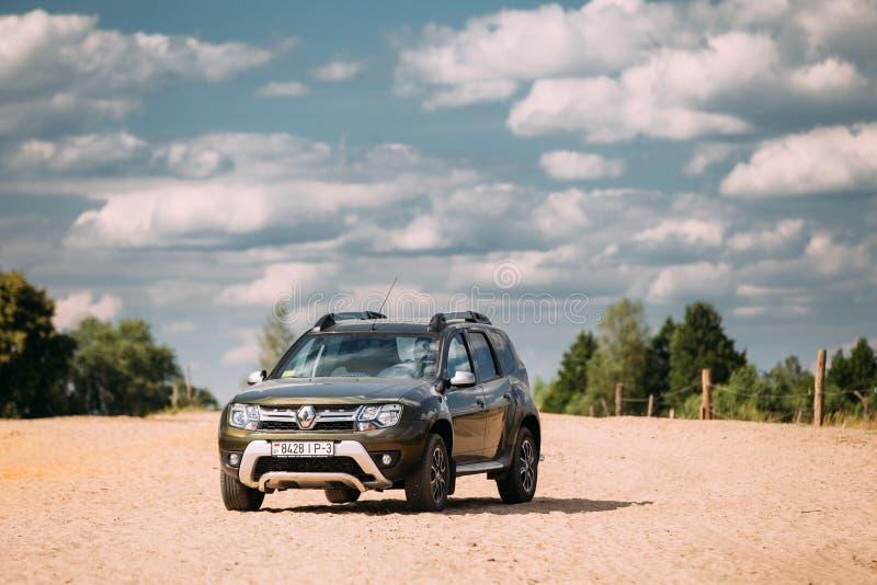 雷诺喷粉器或达基亚喷粉器SUV在乡下风景 喷粉器 免版税库存图片