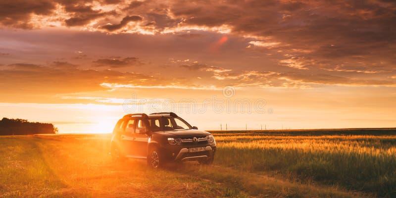 雷诺喷粉器或达基亚喷粉器Suv在路通过夏天麦田在惊人的日落时间 免版税库存照片