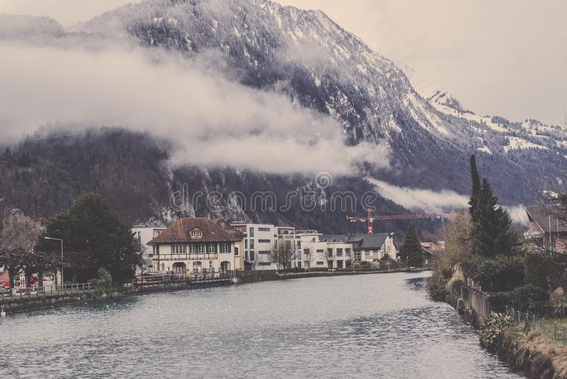 雾和江边村庄围拢的山在烟特勒根 库存照片