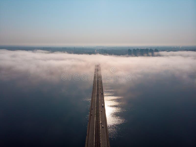 雾或薄雾在河桥梁有汽车通行的在城市、空中全景、早晨阴霾和都市风景 免版税库存图片