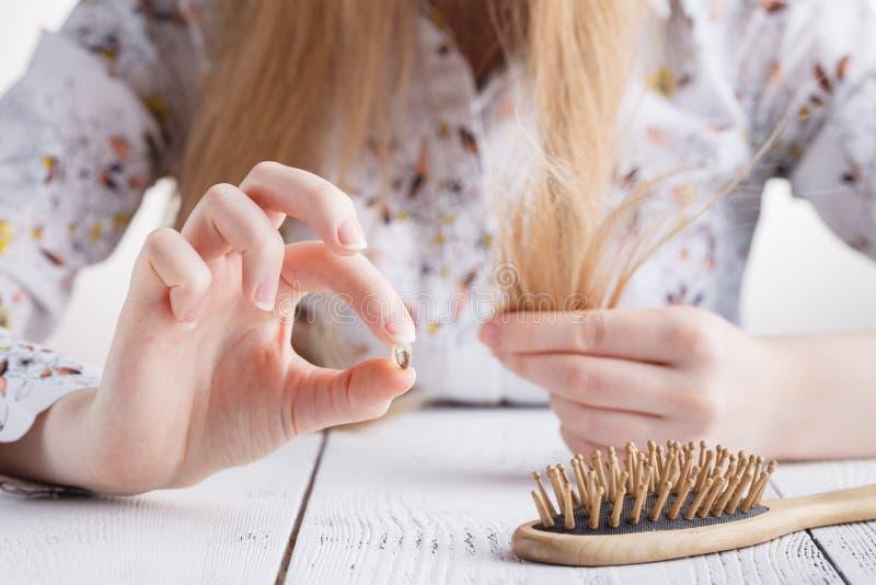 需要更多维生素,有头发问题的妇女,在梳子的失去的头发 免版税库存图片