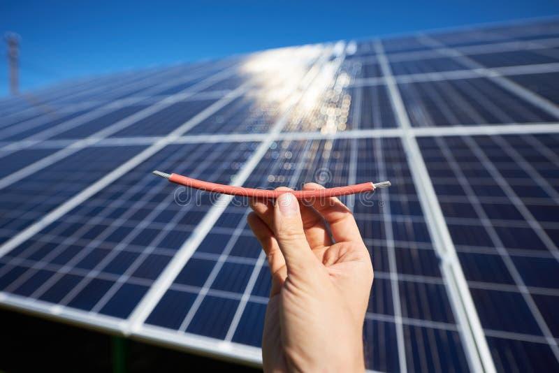 需要通过太阳电池板安装的一部分的红色导线 库存图片